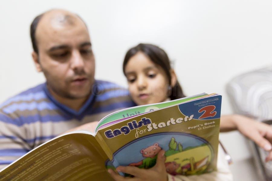 Abends übt Lin mit ihrem Vater Englisch. Usama und Kadija sind mit ihren vier Kindern 2013 vor dem Krieg aus Syrien geflohen und leben seit dem in einer kleinen Zweizimmerwohnung in der türkischen Stadt Gaziantep. © Jan Bosch/GIZ